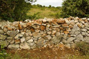 Entretien du mur sur le GR4 à la sortie de Saint-Remèze sur le Dévès.